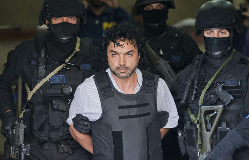 """Police escort alleged Colombian drug lord Henry de Jesus Lopez, alias """"Mi Sangre,"""" or """"My Blood,"""" in Buenos Aires, Argentina, Wednesday, Oct. 31, 2012. Lopez, a former paramilitary wanted in Colombia and the U.S. on charges of organized crime, drug trafficking and terrorism, was arrested in suburban Buenos Aires, Tuesday. (AP Photo/Victor R. Caivano)"""