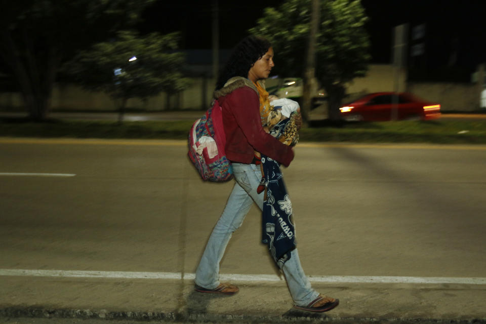 A migrant carrying a young child walks before dawn along the highway to Choloma, Honduras, Thursday, Jan. 14, 2021. About 200 Honduran migrants resumed walking toward the U.S. border, a day before a migrant caravan was scheduled to depart San Pedro Sula. (AP Photo/Delmer Martinez)