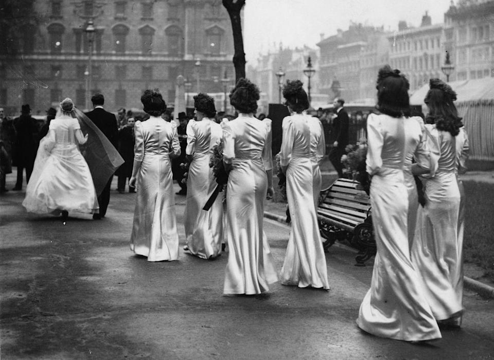 """<p>This society wedding was decidedly luxurious for its time (1938), with bridesmaids clad in very shiny satin in a simple silhouette that was in vogue at the time. </p><p><a href=""""http://www.goodhousekeeping.com/life/relationships/a39750/mother-of-the-groom-bride-horror-stories/"""" rel=""""nofollow noopener"""" target=""""_blank"""" data-ylk=""""slk:10 wedding horror stories »"""" class=""""link rapid-noclick-resp""""><em>10 wedding horror stories »</em></a><br></p>"""