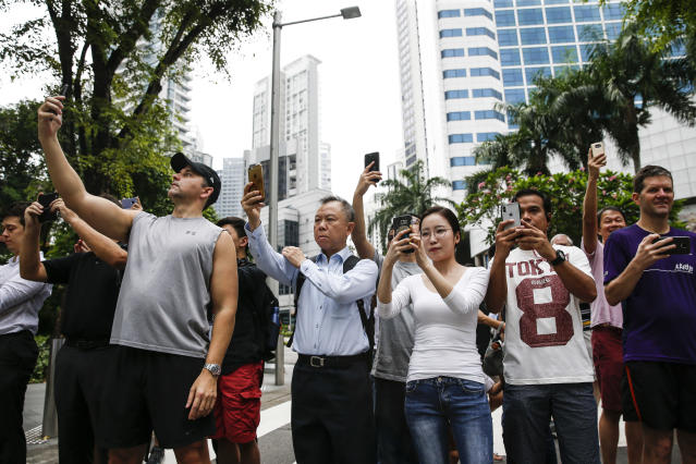 <p>Members of the public take photos of the motorcade of North Korea leader Kim Jong Un as it leaves the St. Regis Hotel on the way to the Capella Hotel in Singapore, Tuesday, June 12, 2018, where the summit between Kim and U.S. President Donald Trump is scheduled. (Photo: Yong Teck Lim/AP) </p>