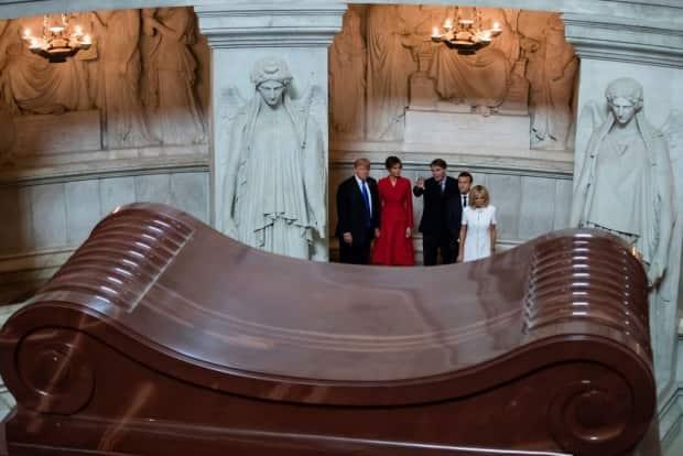 During a visit to Napoleon's tomb at Les Invalides in Paris on July 13, 2017, U.S. President Donald Trump, left, Melania Trump, Macron, second from right, and Brigitte Macron listen to Army Museum director David Guillet, centre.