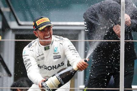 Formula One - F1 - Chinese Grand Prix - Shanghai, China - 09/04/17 - Mercedes driver Lewis Hamilton of Britain celebrates with champagne on the podium after winning the Chinese Grand Prix at the Shanghai International Circuit. REUTERS/Aly Song