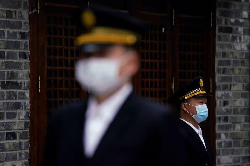Security guards wearing face masks are seen in Wuhan