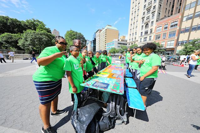 <p>Students from I.S. 117 Joseph H. Wade in the Bronx flash some peace while standing by one of the tables they created in Union Square Park in New York City on June 5, 2018. (Photo: Gordon Donovan/Yahoo News) </p>
