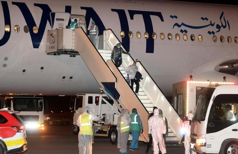 Kuwaitis returning home from Frankfurt are met by health workers in decontamination suits late last month