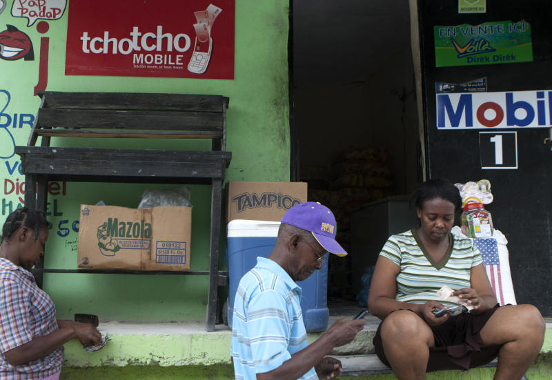 In this June 1, 2012 photo, a vendor of Digicel's Tchotcho Mobile services, right, makes a transfer for a client in front of her shop in Port-au-Prince, Haiti. Aid agencies trying to remake Haiti after a catastrophic earthquake are promoting a new way to bypass banks altogether: easy money transfers by cell phone. The plan lets people save and move money in mobile phone accounts and quickly withdraw it at a network of retail stores around the country. (AP Photo/Dieu Nalio Chery)