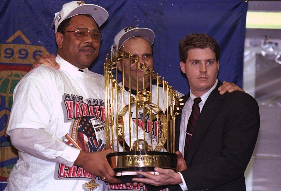 General manger Bob Watson and manager Joe Torre of the New York Yankees hold trophy after winning game six of the World Series against the Atlanta Braves at Yankee Stadium in 1996. (Getty Images)
