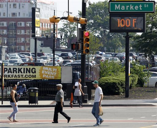 A sign reads 100 degrees as pedestrians cross the street under extreme heat that blanketed the northern New Jersey region, Thursday, June 21, 2012, in Newark, N.J. Forecasters say temperatures could combine with humidity to make it feel like 110 degrees in parts of the state. Thermometers might not drop below 80 in the state's cities during the evening. (AP Photo/Julio Cortez)
