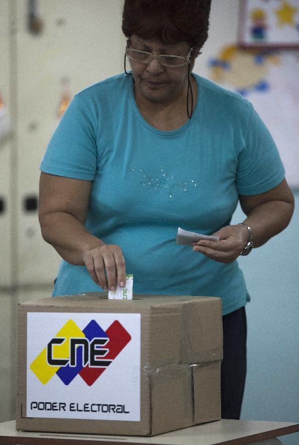 A woman cats his ballot during elections in Caracas, Venezuela, Sunday, Dec. 16, 2012. Venezuelans are choosing governors and state lawmakers in elections that have become a key test of whether President Hugo Chavez's movement can endure if the leader leaves the political stage.(AP Photo/Ariana Cubillos)
