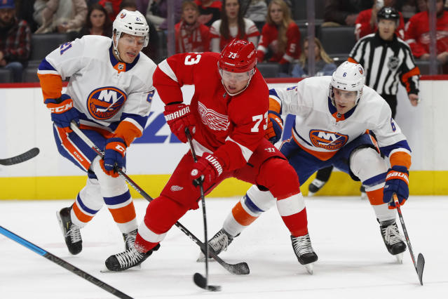 Detroit Red Wings left wing Adam Erne (73) skates past New York Islanders left wing Otto Koivula (21) and Ryan Pulock (6) in the second period of an NHL hockey game Monday, Dec. 2, 2019, in Detroit. (AP Photo/Paul Sancya)