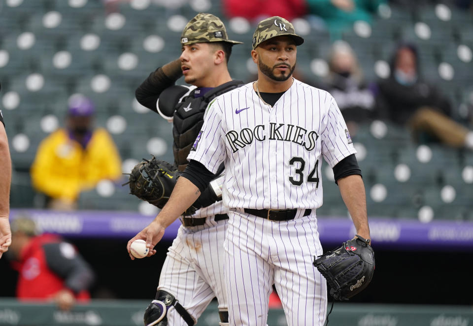 As Colorado Rockies catcher Dom Nunez, back, heads behind the plate, relief pitcher Jordan Sheffield (34) takes a new ball after throwing a wild pitch to allow the go-ahead run to score from third base for the Cincinnati Reds in the ninth inning of a baseball game Sunday, May 16, 2021, in Denver. (AP Photo/David Zalubowski)