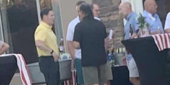 """Arizona Gov. Doug Ducey (left in the yellow shirt) is spotted at a graduation party not wearing a mask despite telling voters to """"Arm yourself with a mask."""""""