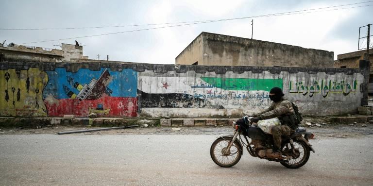 A Syrian man in military fatigues rides a motorbike by a mural-covered wall in the deserted city of Kafranbel, south of Idlib city amid an ongoing pro-regime offensive