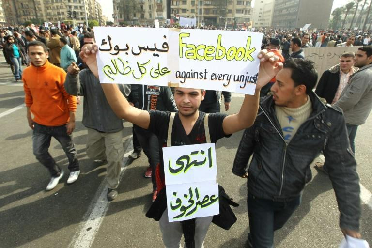 "An Egyptian holds up a sign praising Facebook in 2011 on Cairo's Tahrir Square, heeding a call by the opposition for a ""march of a million"" calling for the ouster of Hosni Mubarak"