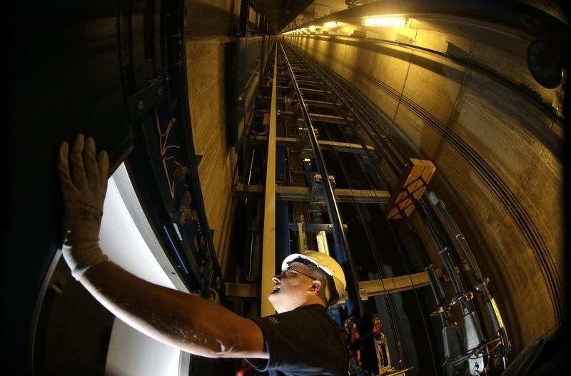 Service engineer of ThyssenKrupp AG inspects door inside elevator shaft in Berlin