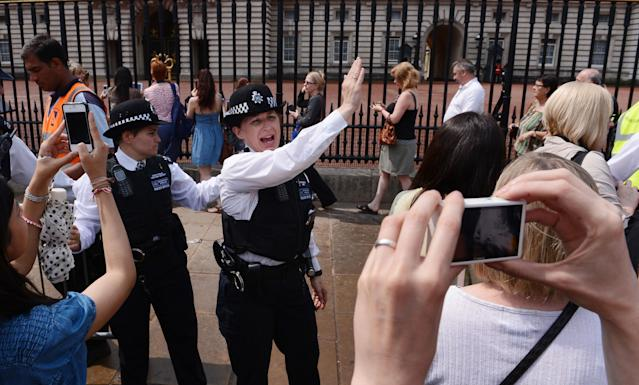 Police officers encourage members of the public, who are queuing to look at the official announcement that the Duke and Duchess of Cambridge have had a baby boy, to keep moving along, outside Buckingham Palace in London.