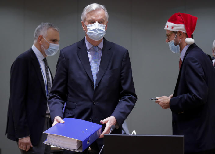 A colleague wears a Christmas hat as European Union chief negotiator Michel Barnier, center, carries a binder of the Brexit trade deal during a special meeting of Coreper, at the European Council building in Brussels, Friday, Dec. 25, 2020. European Union ambassadors convened on Christmas Day to start an assessment of the massive free-trade deal the EU struck with Britain. After the deal was announced on Thursday, EU nations already showed support for the outcome and it was expected that they would unanimously back the agreement, a prerequisite for its legal approval. (Olivier Hoslet, Pool via AP)