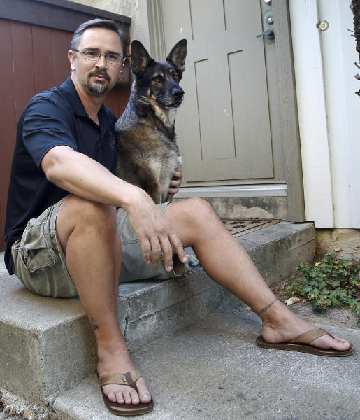 """In this Monday, July 23, 2012 photo, retired U.S. Marine Todd Kennedy poses on his front stoop with his pet, Malcolm, in San Diego. Kennedy served two tours in Iraq. He no longer follows the news there, focusing instead on studying history and anthropology at San Diego State University. """"In any war there are lessons learned. Any war has its skeletons. Any war has its debates, repercussions, its conspiracies. Regardless of whether it was right or wrong to go in to there, for me personally, it's not something I did a lot of dwelling on ... The nation called on me, so it was something I had to do."""" (AP Photo/Lenny Ignelzi)"""