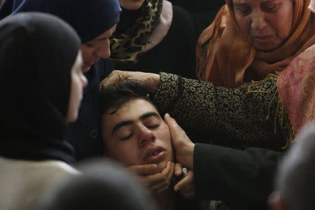 A relative of Palestinian minister Ziad Abu Ein is comforted during his funeral in the West Bank city of Ramallah December 11, 2014. REUTERS/Mohamad Torokman