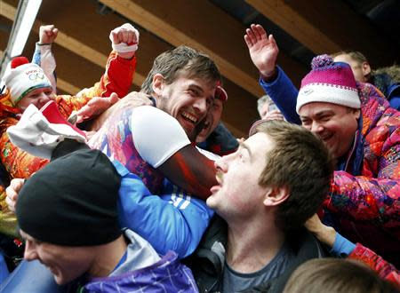 Russia's Alexander Tretiakov (C) celebrates with friends and family after winning the men's skeleton event at the 2014 Sochi Winter Olympics, February 15, 2014. REUTERS/Arnd Wiegmann