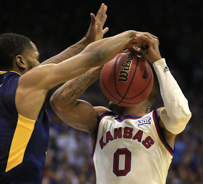 West Virginia guard Tarik Phillip (12) blocks a shot by Kansas guard Frank Mason III (0) during the first half of an NCAA college basketball game in Lawrence, Kan., Monday, Feb. 13, 2017. (AP Photo/Orlin Wagner)
