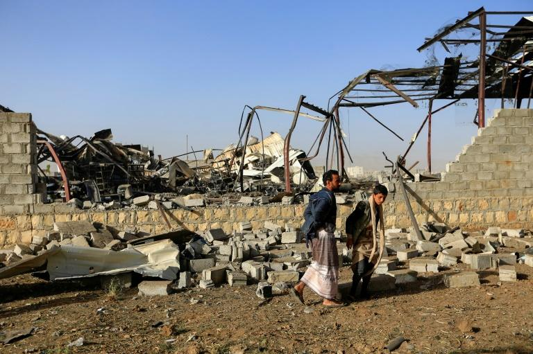 Civilians inspect the damage at a factory after a reported air strike by the Saudi-led coalition in the Yemeni capital Sanaa, on January 20, 2019