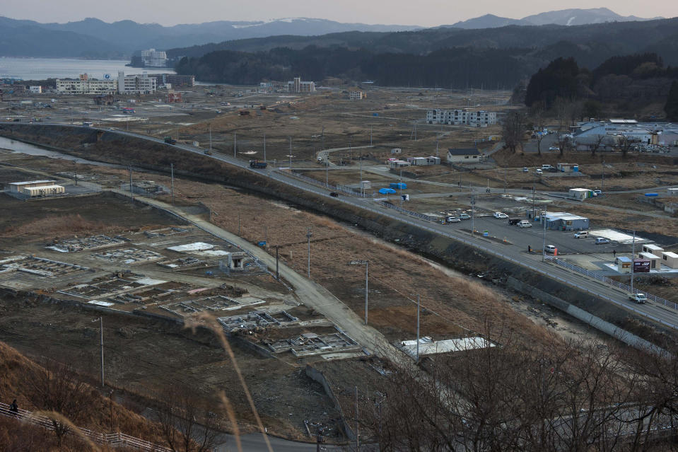 In this Feb. 23, 2012, file photo, Vehicles pass through the ruins of the leveled city of Minamisanriku, Miyagi Prefecture, northern Japan, almost one year after the March 11, 2011 tsunami. (AP Photo/David Guttenfelder, File)