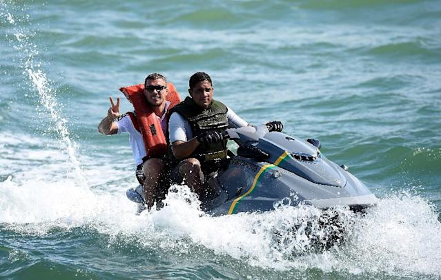 Lukas Podolski (left) was photographed on a jetski as the German football team enjoyed a day off during the 2014 World Cup in Brazil (AFP Photo/MARKUS GILLIAR)