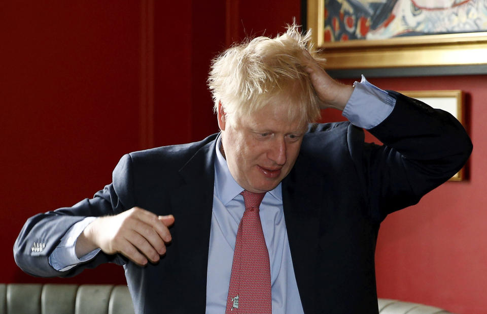Conservative Party leadership candidate Boris Johnson gestures during a visit to Wetherspoons Metropolitan Bar in London, Wednesday July 10, 2019. (Henry Nicholls/Pool Photo via AP)
