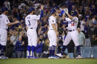 Los Angeles Dodgers' Enrique Hernandez, right, is congratulated by Austin Barnes, center right; Chris Taylor, center left; and Kyle Garlick, left, after hitting a grand slam, as San Francisco Giants catcher Buster Posey stands at the plate during the seventh inning of a baseball game Tuesday, June 18, 2019, in Los Angeles. (AP Photo/Mark J. Terrill)