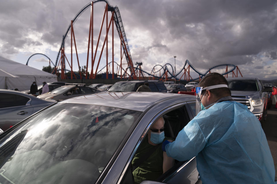 Licensed vocational nurse Joselito Florendo, right, administers the COVID-19 vaccine to Michael Chesler at a mass vaccination site set up in the parking lot of Six Flags Magic Mountain in Valencia, Calif., Friday, Jan. 22, 2021. (AP Photo/Jae C. Hong)