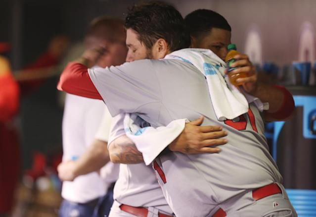 St. Louis Cardinals starting pitcher Lance Lynn, front, hugs catcher Yadier Molina after Lynn retired the Colorado Rockies in the eighth inning of the Cardinals' 8-0 victory in a baseball game in Denver on Monday, June 23, 2014. Lynn earned his eighth win of the season. (AP Photo/David Zalubowski)