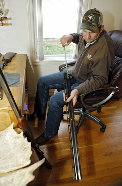 "In this photo taken on Friday, April 12, 2013, Gaspar Perricone, 29, cleans one of his guns at his home in Denver. ""We are pro-gun, there's no two ways about that,"" Perricone said in an interview, stressing that his group opposes bans on assault weapons or high-capacity magazines. ""But we're also mothers and fathers....We don't want to see another Newtown."" Perricone co-founded The Bull Moose Sportsmen's Alliance, a group that took the unusual step earlier this month of releasing a poll that showed wide support among hunters for universal background checks. Most public polls have shown about 90 percent of voters support such a measure. (AP Photo/Ed Andrieski)"