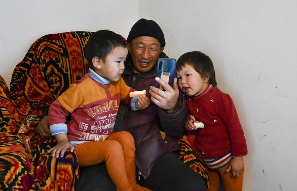Kanat Kaliyev and his grandchildren Aruke, right, and Baisal talk with their relatives on Skype at their family house in the village of Tash-Bashat about 24 kilometers (15 miles) southeast of Bishkek, Kyrgyzstan, Tuesday, Oct. 20, 2020. The political turmoil that has gripped Kyrgyzstan hasn't reached this quiet village in the mountains near the capital, where residents talk about the country's feuding elites with resignation and disdain. (AP Photo/Vladimir Voronin)