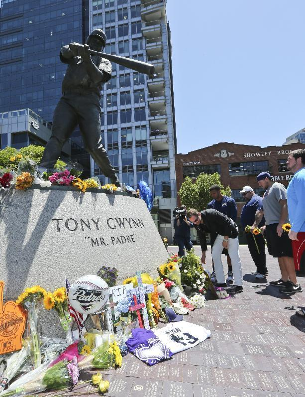 """A.G. Spanos, CEO of the San Diego Chargers, leads his team as they place flowers and other mementos at the base of the Tony Gwynn """"Mr. Padre"""" statue, Monday, June 16, 2014, in San Diego. Gwynn, an eight time National League batting champion with the San Diego Padres and a member of Baseball Hall of Fame, died Monday from cancer. He was 54. (AP Photo/Lenny Ignelzi)"""