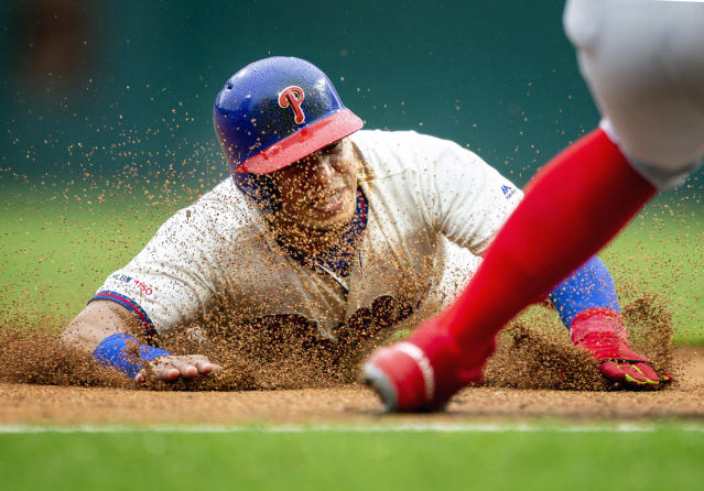 Philadelphia Phillies' Cesar Hernandez (16) steals third base as Washington Nationals' Wilmer Difo, obscured at right, waits for the ball during the fourth inning of a baseball game, Sunday, May 5, 2019, in Philadelphia. (AP Photo/Laurence Kesterson)