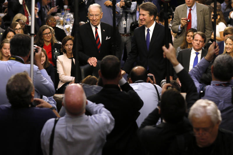 FILE - In this Sept. 4, 2018, file photo Supreme Court nominee Judge Brett Kavanaugh is surrounded by photographers as he stands with Senate Judiciary Committee Chairman Chuck Grassley R-Iowa, during his confirmation hearing on Capitol Hill in Washington. Senate Republicans are moving ahead with Kavnaugh but it's not at all clear if confirming the conservative judge will provide the mid-term election boost once envisioned or saddle the GOP with political fallout from Christine Blasey Ford's allegations of sexual assault for years to come.(Jim Bourg/Pool Photo via AP, File)