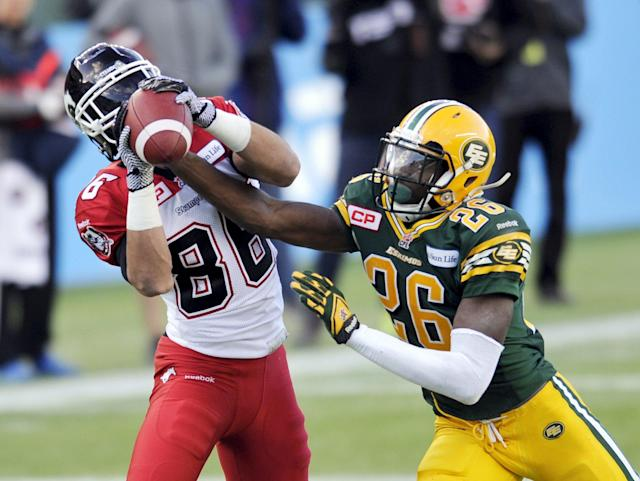 Calgary Stampeders' Anthony Parker (L) has the ball knocked out of his hands by Edmonton Eskimos' John Ojo during their CFL Western Final football game in Edmonton November 22, 2015. REUTERS/Dan Riedlhuber