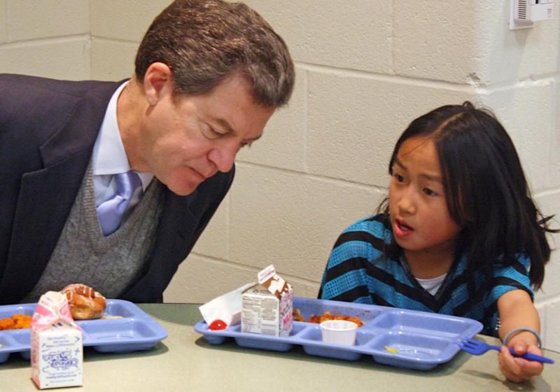 FILE - In this Jan. 23, 2014 file photo Kansas Gov. Sam Brownback, left, leans in to listen to Xen Hesse as the two each lunch at Roesland Elementary School in Roeland Park, Kan. On Friday, March 7, 2014, the Kansas Supreme Court said the state's current public school funding levels are unconstitutional. The case has broader implications beyond the classroom: Kansas enacted sweeping cuts to income taxes championed by Brownback that have reduced the amount of available resources to comply with a court order. (AP Photo/John Milburn, File)