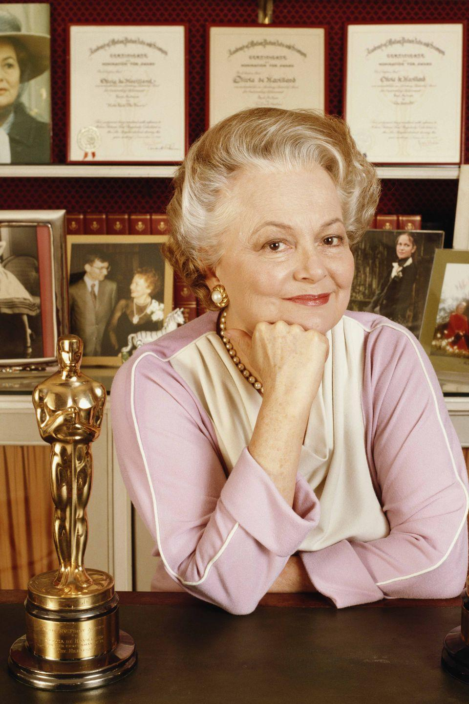 <p>Olivia posing with her Academy Award in 1990.</p>
