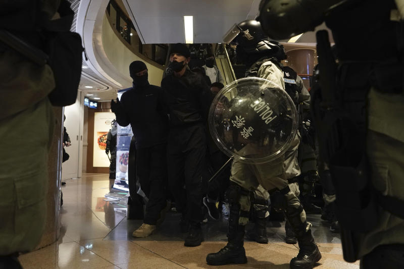 Riot police take away protesters in a mall during a rally on Christmas Eve in Hong Kong on Tuesday, Dec. 24, 2019. More than six months of protests have beset the city with frequent confrontations between protesters and police. (AP Photo/Kin Cheung)