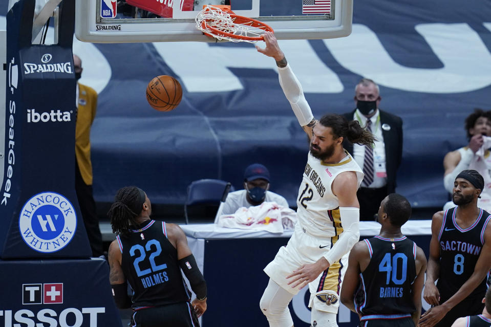 New Orleans Pelicans forward Zion Williamson (1)2 slam dunks over Sacramento Kings center Richaun Holmes (22) in the first half of an NBA basketball game in New Orleans, Monday, April 12, 2021. The Pelicans won 117-110. (AP Photo/Gerald Herbert)