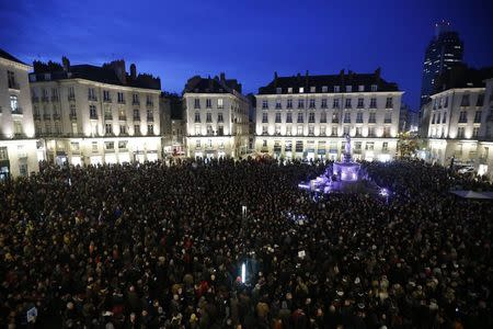 People gather to pay tribute at the Place Royal in Nantes January 7, 2015, following a shooting by gunmen at the Paris offices of weekly satirical magazine Charlie Hebdo. Gunmen stormed the Paris offices of the weekly satirical magazine Charlie Hebdo, renowned for lampooning radical Islam, killing at least 12 people, including two police officers in the worst militant attack on French soil in recent decades. The French President headed to the scene of the attack and the government said it was raising France's security level to the highest notch. REUTERS/Stephane Mahe (FRANCE - Tags: POLITICS CRIME LAW CIVIL UNREST)