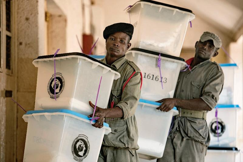 Security staff carry ballot boxes at a polling station in Tanzania's commercial capital Dar es Salaam on October 26, 2015 (AFP Photo/Daniel Hayduk)