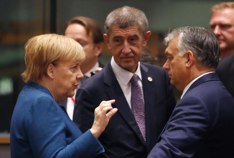 German Chancellor Angela Merkel, left, speaks with Hungarian Prime Minister Viktor Orban, second right, during a round table meeting at EU summit in Brussels, Friday, Oct. 18, 2019. After agreeing on terms for a new Brexit deal, European Union leaders are meeting again to discuss other thorny issues including the bloc's budget and climate change. (AP Photo/Frank Augstein)