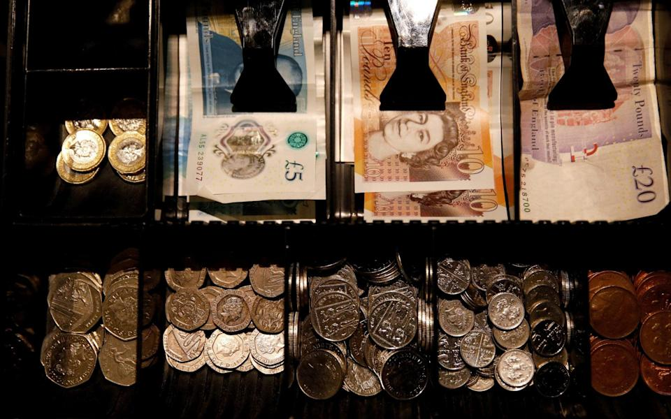 Pound Sterling notes and change are seen inside a cash resgister in a coffee shop in Manchester - PHIL NOBLE/Reuters