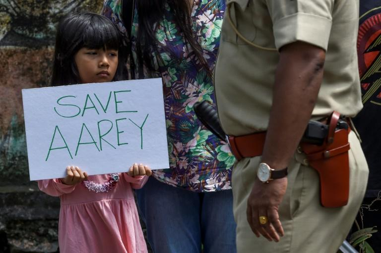 A policeman walks past a child holding a poster as she protests against the destruction of Aarey forest