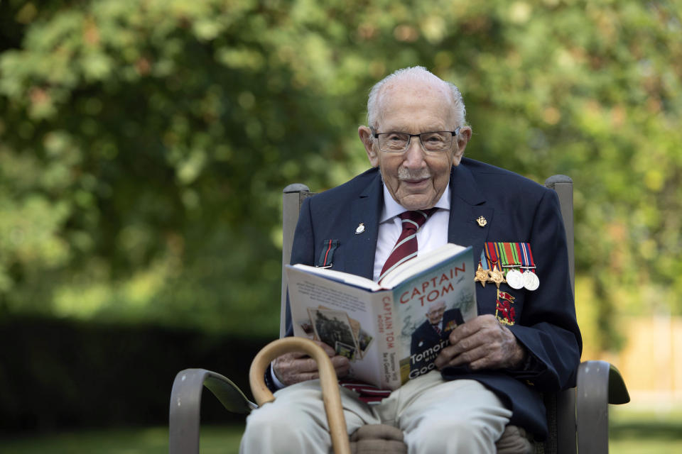 Captain Sir Tom Moore poses with his new autobiography, Tomorrow Will Be A Good Day published Thursday Sept. 17, 2020, at his home in Marston Moretaine, England.  Captain Tom's autobiography covers his notable military career and rising to fame at aged 100, lauded for raising millions of pounds for Britain's Nation Health Service charity by walking laps of his Bedfordshire garden. (Joe Giddens/PA via AP)