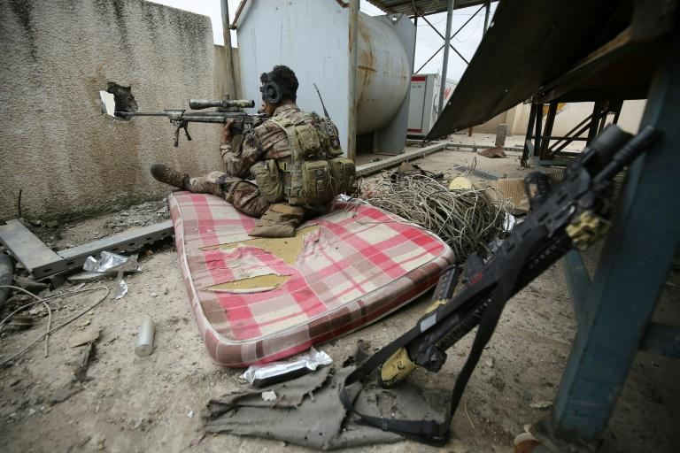 An Iraqi forces sniper takes aim as federal police and the elite Rapid Response Division battle to take the Old City in west Mosul from jihadists