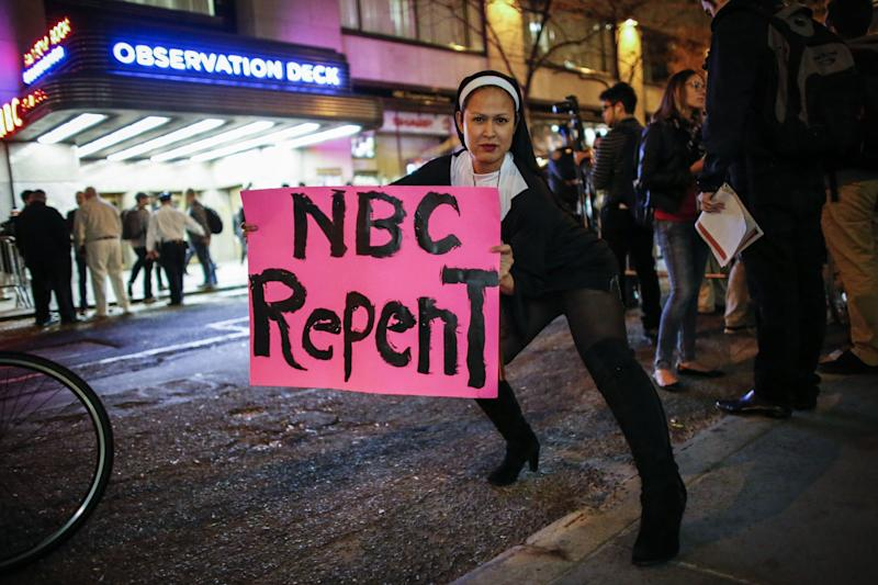 A woman dressed as nun holds a poster as she poses for a photo during a protest in front of NBC studios while they are calling for the network to rescind the invitation to Donald Trump to host Saturday Night Live show on November 4, 2015 in New York.